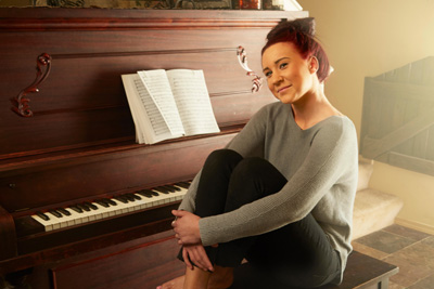 EYCW0M Portrait of young woman sitting on piano stool hugging knees